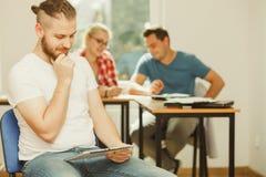 Menino do estudante com a tabuleta na frente de seus colegas Foto de Stock