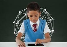 Menino do estudante na tabela usando uma tabuleta contra o quadro-negro verde com gráfico da educação fotografia de stock
