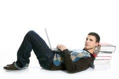 Menino do estudante que encontra-se no assoalho, nos livros e no computador Imagem de Stock Royalty Free