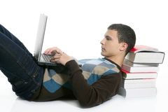 Menino do estudante que encontra-se no assoalho, nos livros e no computador imagens de stock
