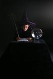 Menino do feiticeiro que escreve um encanto Fotos de Stock Royalty Free