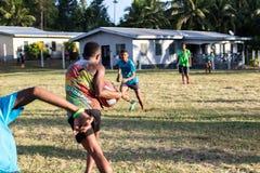 Menino do Fijian que joga a jarda de escola do competitve do rugby foto de stock