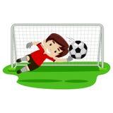 Menino do goleiros que tenta travando a bola na porta do futebol Foto de Stock