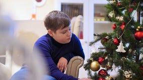 Menino do jovem adolescente que senta-se em uma cadeira perto da árvore de Natal Olha os brinquedos, pendura na árvore de Natal