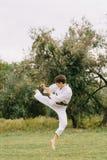 Menino do karaté na ação Treinamento do judô em um fundo do parque Conceito de combate Copie o espaço Imagens de Stock