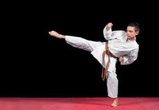 Menino do karaté na luta branca do quimono isolado no fundo preto Fotografia de Stock