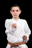 Menino do karaté na luta branca do quimono isolado no fundo preto Imagens de Stock Royalty Free