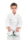 Menino do karaté que senta-se no quimono branco fotografia de stock