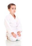 Menino do karaté que senta-se no quimono branco Imagens de Stock Royalty Free