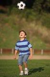 Menino do Latino que joga com esfera de futebol fotografia de stock royalty free
