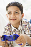 Menino do Oriente Médio que joga um jogo video fotografia de stock