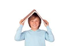 Menino do Preteen com um livro grande oh sua cabeça fotos de stock
