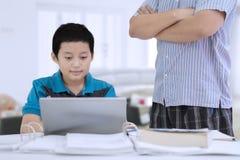 Menino do Preteen supervisionado por seu pai em casa imagem de stock royalty free