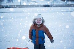 Menino do retrato com tubulação na neve, inverno, conceito da felicidade Imagens de Stock Royalty Free