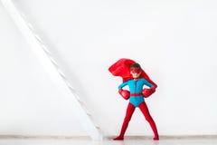 Menino do super-herói em luvas de encaixotamento vermelhas e um cabo no vento
