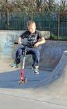 Menino do 'trotinette' no parque do patim Fotografia de Stock