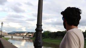 Menino do turista perto de Arno em Florença filme
