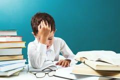 Menino do ute do ¡ de Ð que lê o livro difícil na tabela, fundo azul foto de stock