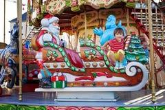 Menino doce, montando em um pequeno trenó de Santa Claus em um carrossel Imagem de Stock
