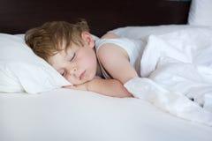 Menino doce pequeno da criança que dorme em sua cama foto de stock