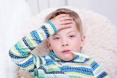 Menino doente com o termômetro que coloca na cama e que toma a temperatura fotografia de stock royalty free