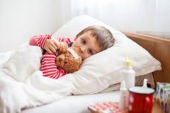 Menino doente da criança que encontra-se na cama com uma febre, descansando imagens de stock