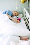 Menino doente na cama de hospital com seu brinquedo Fotografia de Stock Royalty Free