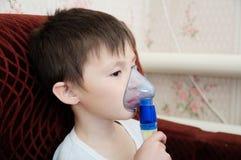 Menino doente na máscara do nebulizer que faz a inalação, o procedimento respiratório pela pneumonia ou a tosse para a criança, i fotos de stock