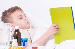 Menino doente no livro de leitura da cama imagem de stock