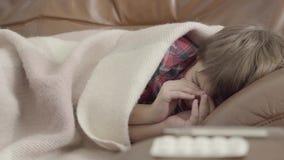 Menino doente pequeno do retrato que encontra-se no sofá coberto com uma cobertura em casa que espirra Comprimidos diferentes que filme