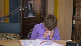 Menino doente que funde seu nariz em um guardanapo ao sentar-se em uma tabela em casa vídeos de arquivo