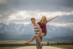 Menino dos adolescentes e uma menina na estrada perto das montanhas Fotos de Stock