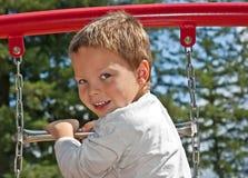 Menino dos anos de idade 4 no equipamento do campo de jogos Fotografia de Stock