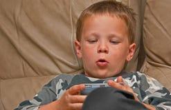 Menino dos anos de idade 5 com os Freckles que jogam o jogo video Fotografia de Stock Royalty Free
