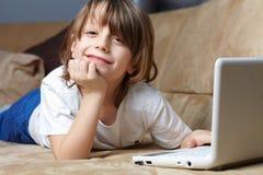 menino dos anos de idade 6 que encontra-se no sofá com seu portátil Foto de Stock