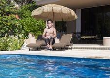 Menino dos anos de idade onze que faz uma bala de canhão em uma piscina Fotografia de Stock Royalty Free