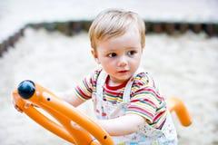 Menino dos anos de idade que balanç em um balanço Foto de Stock