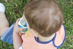 menino dos anos de idade 2 que come um iogurte que senta-se na grama Foto de Stock