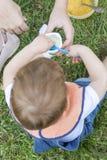 menino dos anos de idade 2 que come um iogurte que senta-se na grama Fotografia de Stock