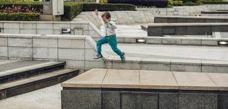 menino dos anos de idade 5 que corre em torno da cidade Imagem de Stock