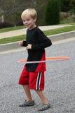 Menino dos anos de idade seis que exercita com uma aro do hula Foto de Stock