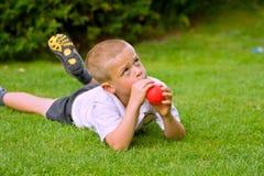 Menino dos anos de idade seis que prende um balão Foto de Stock