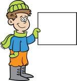 Menino dos desenhos animados na roupa do inverno que guardara um sinal Foto de Stock Royalty Free