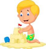 Menino dos desenhos animados que faz o castelo da areia Foto de Stock
