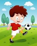 Menino dos desenhos animados que joga o futebol Fotos de Stock