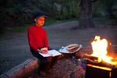 Menino e acampamento da noite Foto de Stock Royalty Free