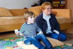 Menino e avó da criança que jogam o jogo de vídeo imagem de stock royalty free