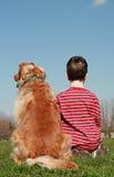 Menino e cão que sentam-se em um monte Imagem de Stock
