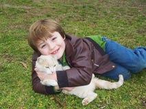 Menino e gato que relaxam no campo Imagem de Stock