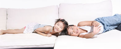Menino e girlplaying e rir no sofá fotografia de stock royalty free